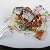 Coca de sardina ahumada, tomate concassé y polvo de piñones